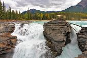 Howling Athabasca Falls in the Rocky Mountains of Canada. Between the cliffs above the water stuck l