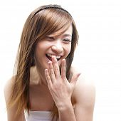 Laughing Asian woman covering her mouth on white background