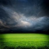 Dark Cloudy Sky And Green Grass Meadow