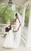 African American bride dancing with flower girl