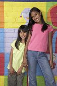 Pacific Islander girls in front of mural