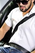 picture of seatbelt  - Young man in sunglasses sitting in a car with seatbelt on - JPG
