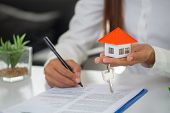 House Model And Keys In The Hands Of Business People. A Woman Signs A Contract To Purchase A Home Wi poster