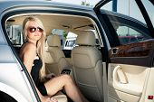 Young blond lady sitting on a backseat of a luxury car