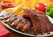 stock photo of barbecue grill  - Two racks of barbecued pork baby back ribs with french fries and dipping sauce - JPG