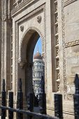 picture of cameos  - Vertical take of the Gateway of India its black painted railings with a cameo view of the Taj Hotel from an angled view of an archway - JPG