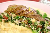 stock photo of tabouleh  - Sliced Middle Eastern lamb fillet with hommus and tabouleh - JPG