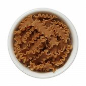 Uncooked Brown Wholewheat Pasta In A Bowl Isolated On White Background