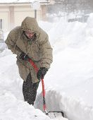 stock photo of snow shovel  - A young man shoveling deep snow in a very cold blizzard - JPG