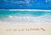 welcome written in a sandy tropical beach