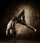 Toned picture of young man with naked torso doing acrobatic movements