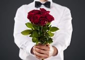 Man giving bouquet of red roses