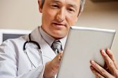 Close up of mature male doctor using digital tablet