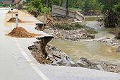 picture of flood  - Destroyed road left with debris after river flooding - JPG
