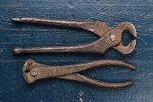 old rusty tongs on blue table