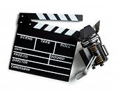 top view of clapper board and movie light on white background