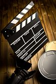 clapper board with movie light and film reels on wooden table