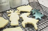 stock photo of shortbread  - Baking homemade Christmas shortbread cookie biscuits in reindeer bells santa boot and tree shapes on blue and white shabby chic table - JPG