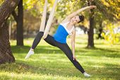 Anti-gravity Yoga, woman doing yoga exercises in the park