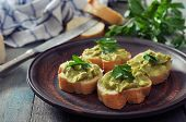 stock photo of canapes  - Delicious appetizer canapes of bread and guacamole served with parsley closeup - JPG