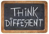 think different - motivational phrase - white chalk handwriting on a vintage slate blackboard