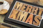 Merry Xmas in letterpress wood type on digital tablet computer with stylus pen, coffee cup and cooki