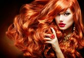 Long Curly Red Hair. Fashion Woman Portrait. Beauty Model Girl with Luxurious Hair, Make up and Acce
