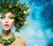 Christmas Winter Woman. Beautiful New Year and Christmas Tree Holiday Hairstyle and Make up. Beauty Fashion Model Girl over Snow Background with Snowflakes. Creative  Hair style decorated with Baubles
