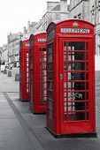 A row of classic British phone boxes on The Royal Mile, Edinburgh, Scotland. Retro effect in black a