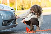 Beautiful woman assembling towing hook to a broken car and holding tow rope in the other hand