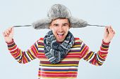 Happy handsome man in striped sweater, scarf and a furry hat posing over a blue background poster