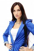 Portraif of a beautiful brunette woman with necklace and blue jacket who is posing over a white background
