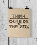 stock photo of thinking outside box  - poster with think outside the box on a wood wall - JPG