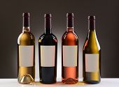 Four Wine Bottles with blank labels on a light to dark gray background. Four different wines includi