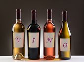 Four Wine Bottles with their labels spelling out the word VINO, on a light to dark gray background.