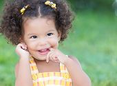pic of diffusion  - Cute hispanic girl with an afro hairstyle laughing with diffused green grass background - JPG
