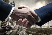 image of cuff  - Close up of businessmen shaking hands with cityscape in the background - JPG