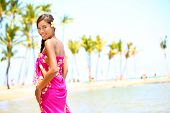 Beach travel - woman smiling happy on Hawaii. Girl in sarong cheerful on sunny hawaiian palm tree be