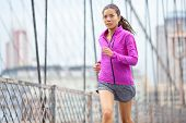 Female runner running and jogging in New York City. Woman sport athlete training outdoor for marathon living healthy lifestyle. Image from Brooklyn Bridge, New York City, USA. Asian Caucasian model.