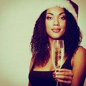 christmas young beautiful mulatto woman smiling with champagne and in santa's hat, toned