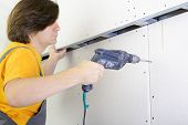 Man using drill to attach drywall panel to wall