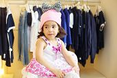 Pretty little girl in funny hat and dress in children clothing store.