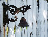 Vintage cast-iron bell on white painted fence