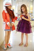 Girl in violet dress with flower stands near mannequin in children store.
