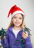 Portrait of girl in Santa hat holding fairy lights during Christmas at home