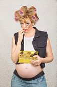 image of hillbilly  - Expectant hillbilly in curlers eating box of chocolates - JPG