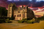 stock photo of yellow castle  - Picture of Belfast Castle in Northern Ireland during a colorful Sunset - JPG