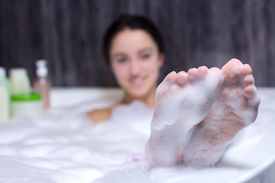 picture of douching  - Beautiful smile woman washing leg with pink sponge in bath - JPG