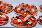 foto of oregano  - Home baked vegan mini pizza with olives red pepper tomato pear oregano and pesto on parchment paper - JPG