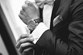stock photo of watch  - Close up of elegant man in suit with watch on hand - JPG